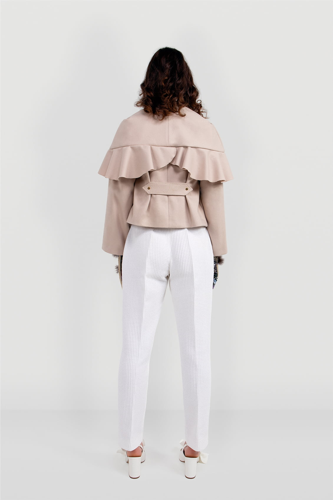 Back of the beige wool women's coat AUDREY. Hip-length single-breasted coat with attachable cape detail. Designer garment made in the UK.