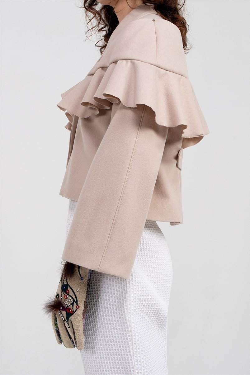 Side of the AUDREY coat. Beige wool women's coat is hip-length, single-breasted with attachable cape. Designer garment made in the UK.