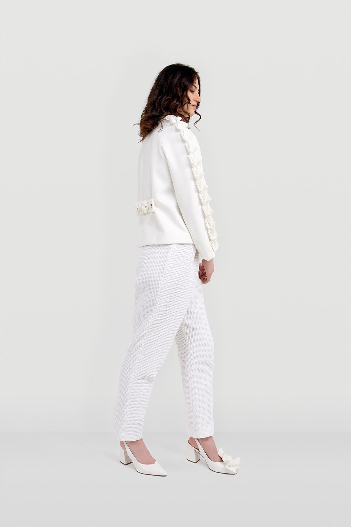 Side of the white wool women's coat ALIA with origami decorated sleeves. Designer made-to-measure garment made in the United Kingdom