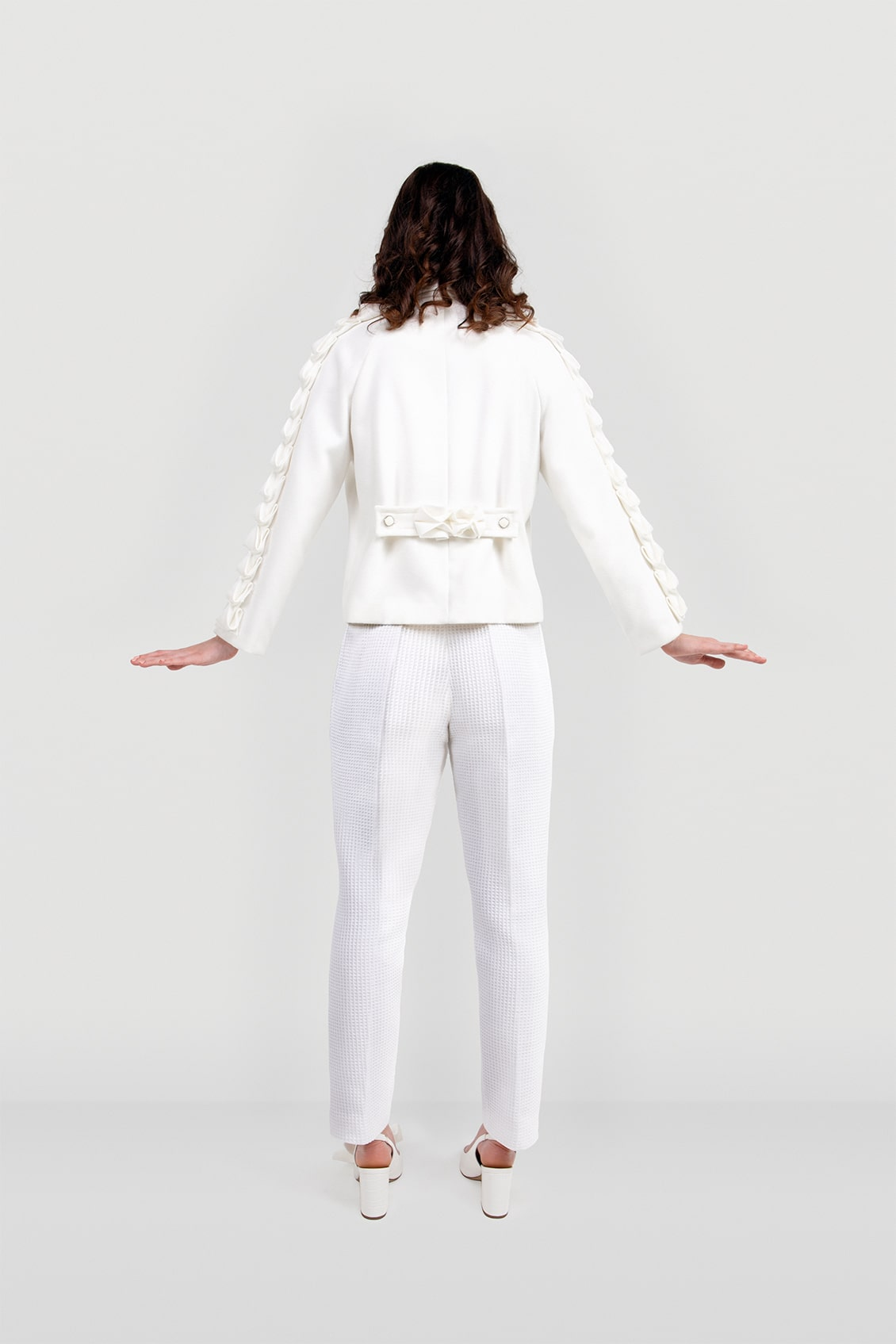 Back of the luxury white wool women's coat ALIA with origami decorated sleeves. Designer made in the United Kingdom