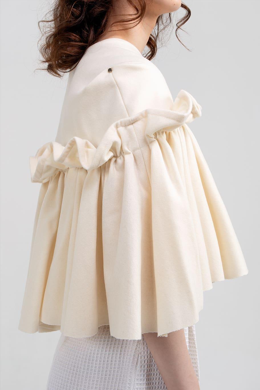 VALDONE Au - Close up of the side of the cream colour British wool designer cape HAZEL