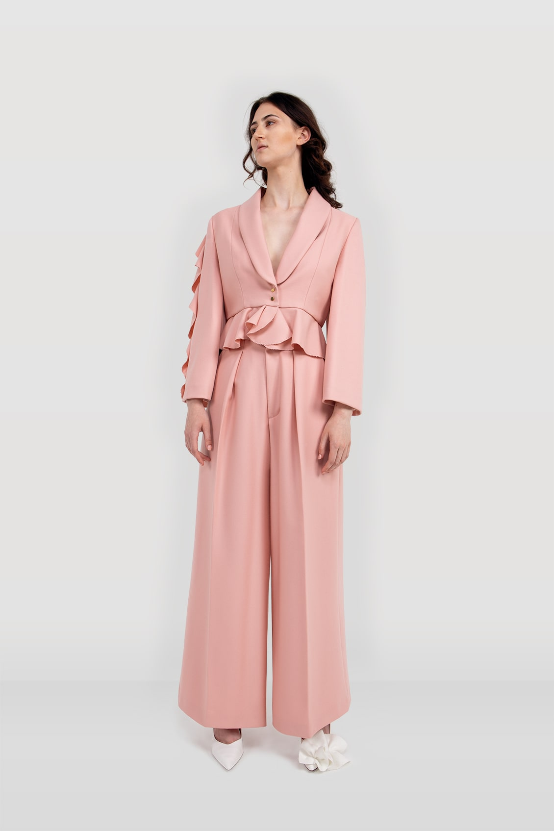 Front of the baby pink, designer women's tailored suit jacket 'ALYSA' with wide sleeves and ruffles along the right sleeve and the hem.