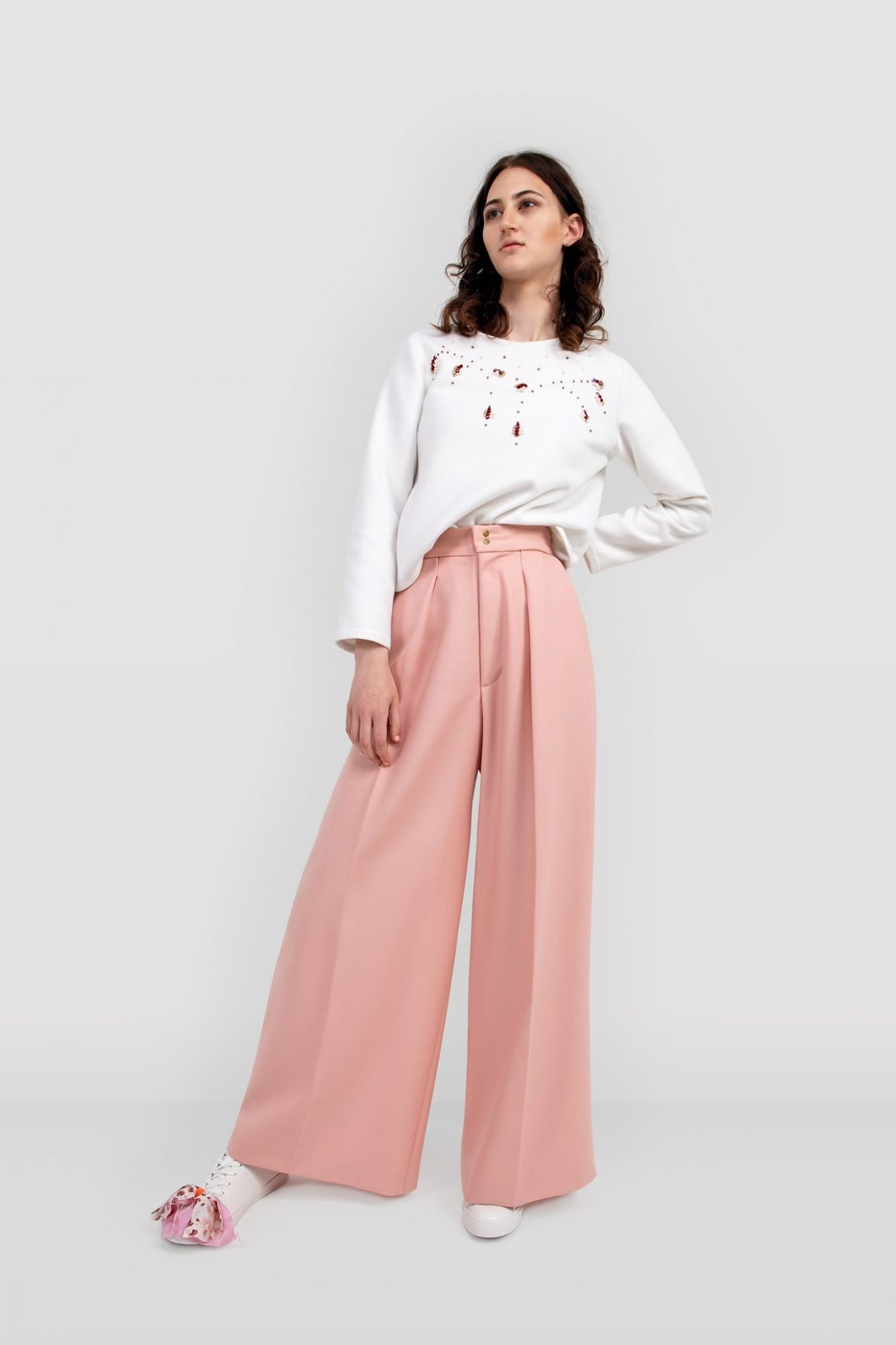 Front of the women's tailored suit trousers ALYSA. High-waisted trousers are cut from a fine wool fabric in a blush pink colour. Made in the UK.